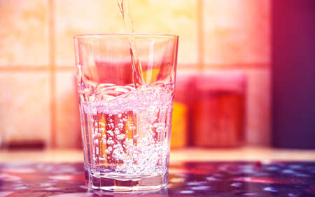 Glass of pure water on kitchen table Фото со стока