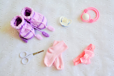 baby stuff: Collection of baby things for girl: booties, pacifier, socks, bow, scissors, rattle on white background. Top view.