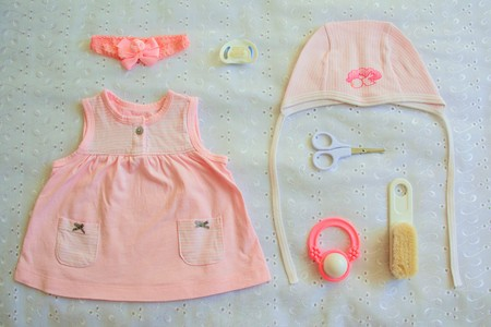 nipple girl: Collection of baby things for girl, top view. Dress, pacifier, comb, bow, scissors, rattle, cap, nipple on white background.