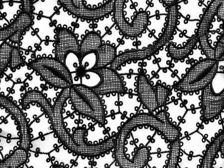 white silk: Black lace ornament on white silk background