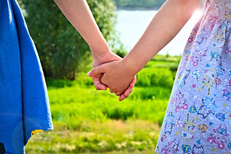 Two children holding hands near the river
