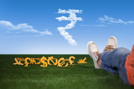 Rich and successful young man is sitting with money on grass
