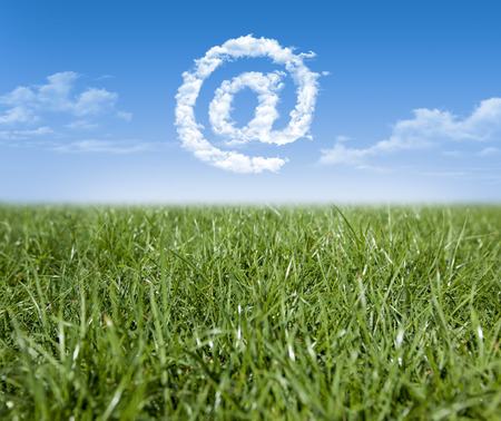 unsettled: Green grass and at sign shaped clouds Stock Photo