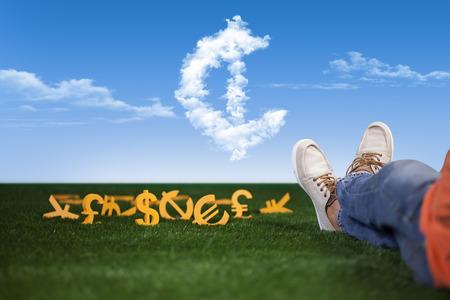 libra esterlina: joven rico y exitoso está sentado en la hierba con el dinero Foto de archivo