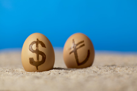Universal money icon painted on eggs on the sand Stock Photo
