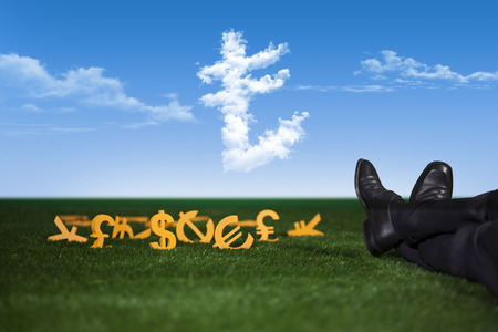 Rich and successful businessman is sitting with money on grass Stock Photo