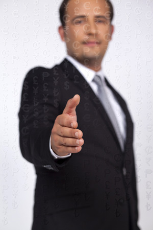 reach out: Businessman reach out a hand to deal front of the worlds money icons Stock Photo