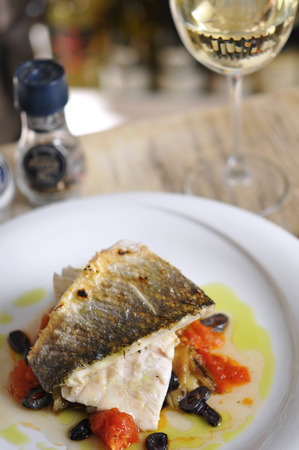 Grilled fish and garnitures in plate and white wine on wooden table