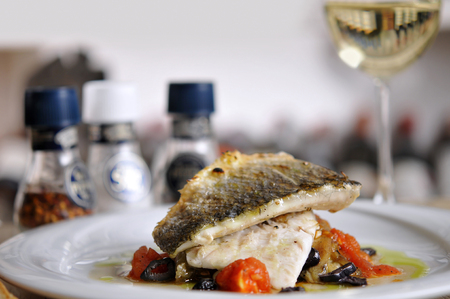 garniture: Grilled fish and garnitures in plate and white wine on wooden table