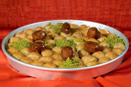 baklawa: baklava sweet pastry in a tray on red table Stock Photo