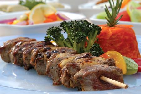 garniture: Shish kebab lamb meat and vegetables in the dish