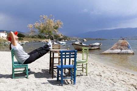 characteristic: Woman is resting at characteristic restaurant on coast of the lake