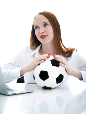 Beautiful long haired girl holding a soccer ball and sit on a desk