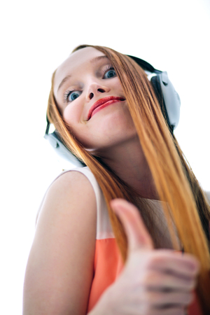 headed: Long haired red headed girl with headphones listening to music Stock Photo