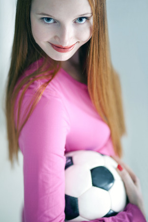 fanatic: Beautiful long haired girl holding a soccer ball Stock Photo