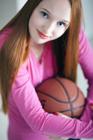 fanatic: Attractive long haired holding a basketball ball and sitting on floor