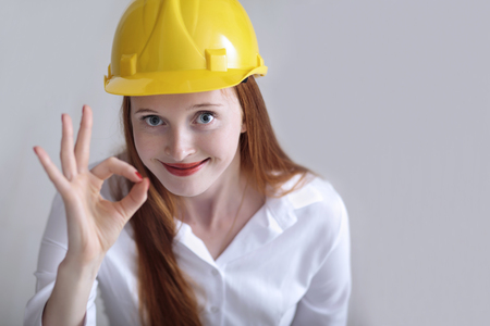okey: Young beautiful female with yellow helmet showing the okey sign Stock Photo