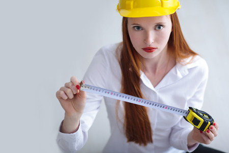 Long haired red headed woman holding a tape measure and wearing a safety hat Stock Photo