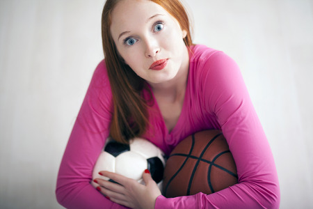 fanatic: Young girl holding soccer and basketball balls and sitting on floor Stock Photo