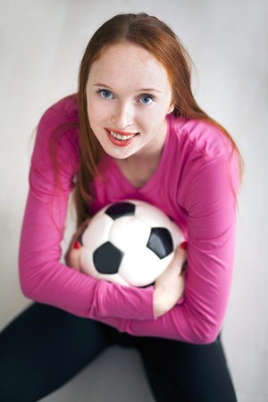 fanatic: Beautiful blond girl holding a soccer ball and sitting on floor Stock Photo