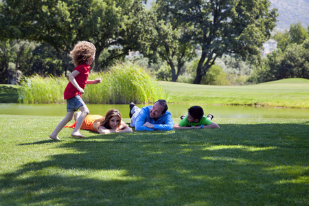 Happy family is lying down on the grass at park Stock Photo