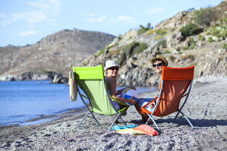 chaise lounge: Young couple is sitting on chaise lounge at the beach Stock Photo