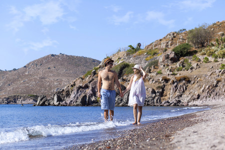 short wave: Young couple is walking on the beach hand to hand