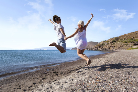 Young couple is jumping on the beach hand to hand Stock Photo