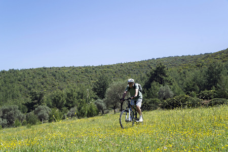 casque: Cyclist man is biking in a green field on a spring day