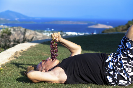 deposition: Tired old man is lieing and eating grapes cheerfully