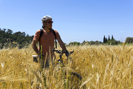 Cyclist man is resting ia gleanings field Stock Photo