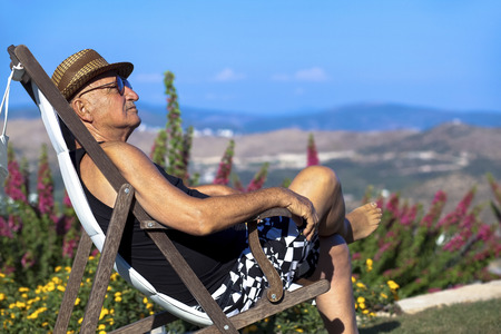 cheerfully: Tired old man is sitting cheerfully and confidently