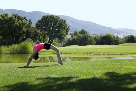 Young woman is doing yoga on green grass at park