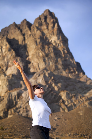 Healthy and happy young woman greets the mountains