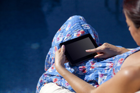 poolside: carefree woman uses touch pad tablet technology at the poolside Stock Photo