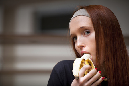 banana: Woman is sitting in sport saloon and eating banana