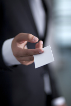 businesscard: Businessman holding an white blank business card