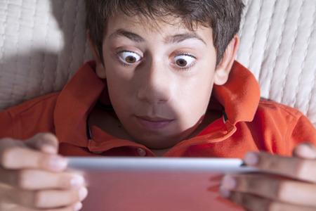 niños jugando videojuegos: niño conmocionado está jugando con tablet PC