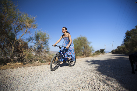 Young woman is riding bycle at a natural road