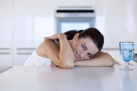 Young woman is sitting in the kitchen Stock Photo