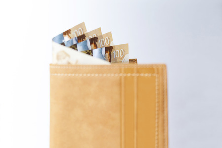 Canadian Dollars and credit cards in mustard coloured leather wallet Stock Photo - 73476292