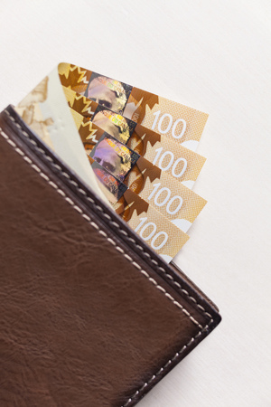 Canadian Dollars and credit cards in brown coloured leather wallet Stock Photo - 74699299