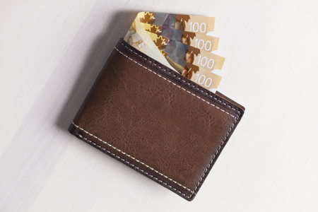 Canadian Dollars and credit cards in brown coloured leather wallet Stock Photo - 74699303