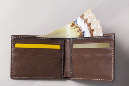 Canadian Dollars and credit cards in brown coloured leather wallet Stock Photo - 74699307