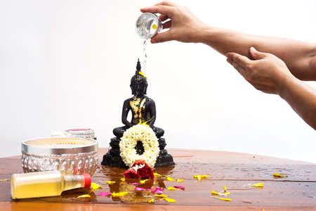 hand pour water on head buddha statue for  worship in songkran festival