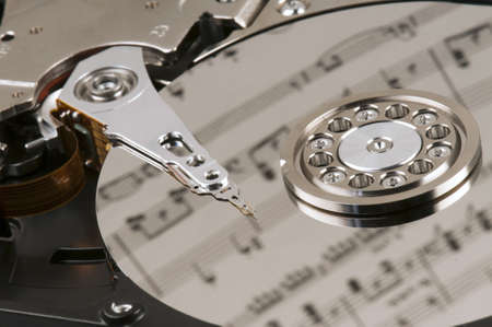 Close-up of the inside of a hard disk reflecting sheet music Stock Photo