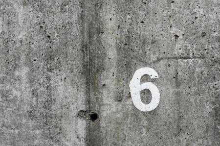 numéro six sur fond de mur en béton cru Banque d'images