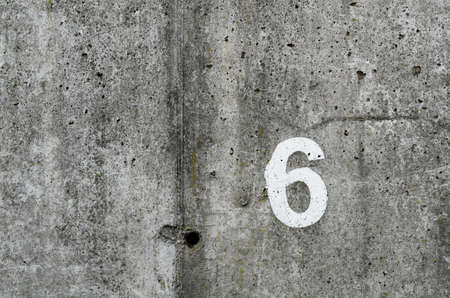 number six on vintage concrete wall background photo