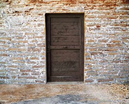 antigua puerta de madera en la pared de ladrillo
