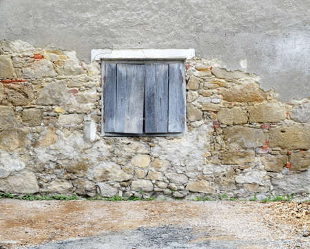 detail of country house stone wall with wooden window shutter photo